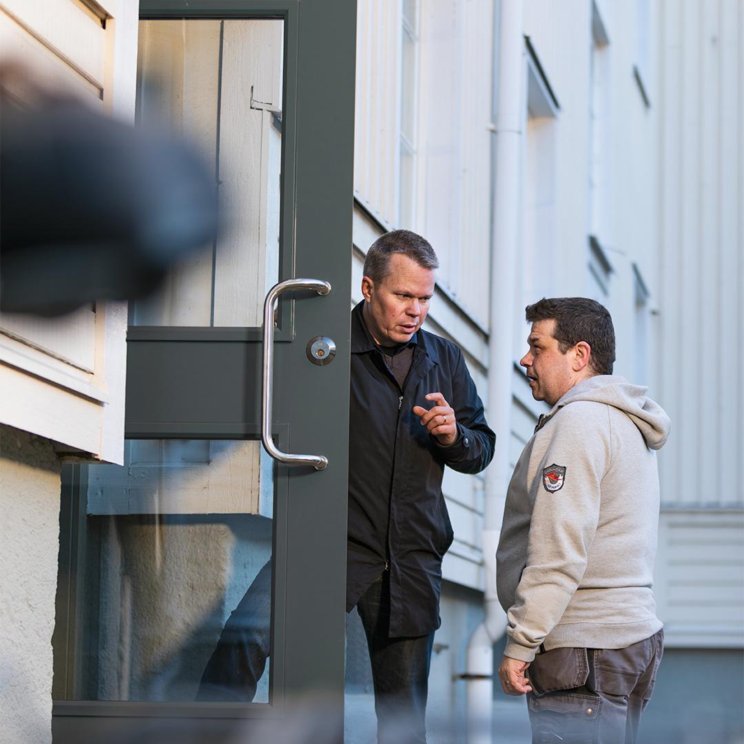 Två män diskuterar resultatet av installerade entrédörrar från Daloc